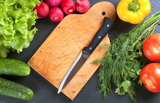 Свежие овощи и разделочная доска с ножом на черной грифельной доске. вид сверху.