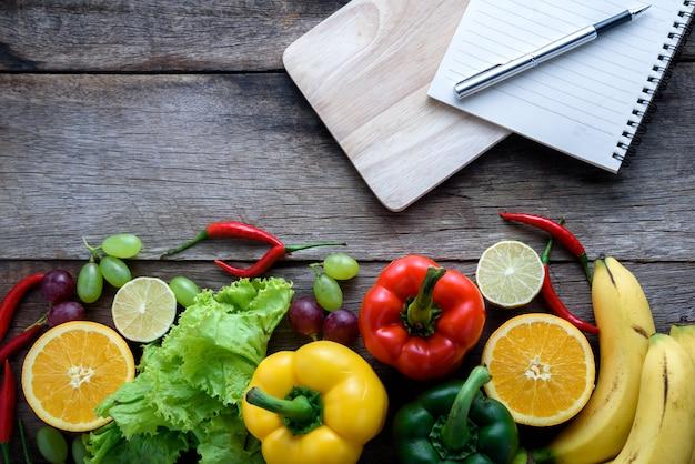 新鮮な野菜や果物、木製の背景上のフィットネスディナーのためのトップビュー、食品コンセプト