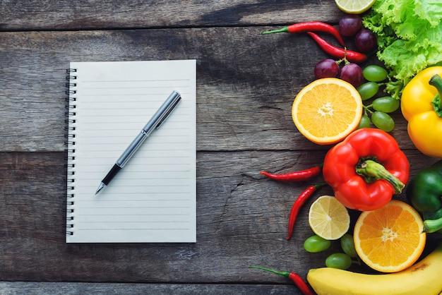 新鮮な野菜や果物、木製の背景上にフィットネスディナー