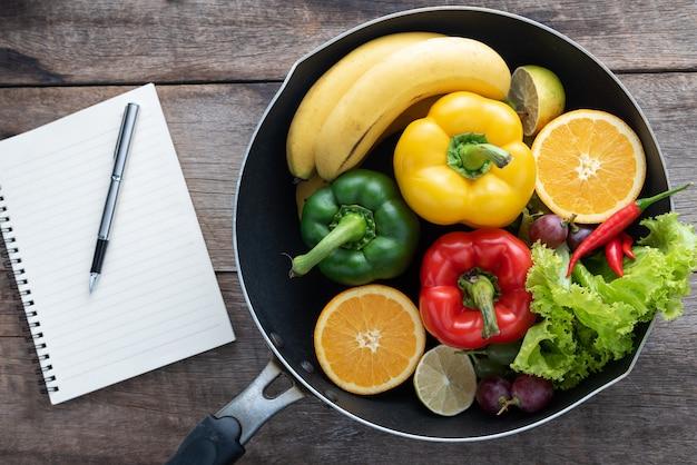 新鮮な野菜や果物の木製の背景の上のフィットネスディナー