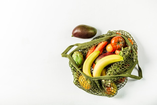 Свежие овощи и фрукты в зеленой сумке. нет пластика, только натуральные материалы и натуральные продукты.