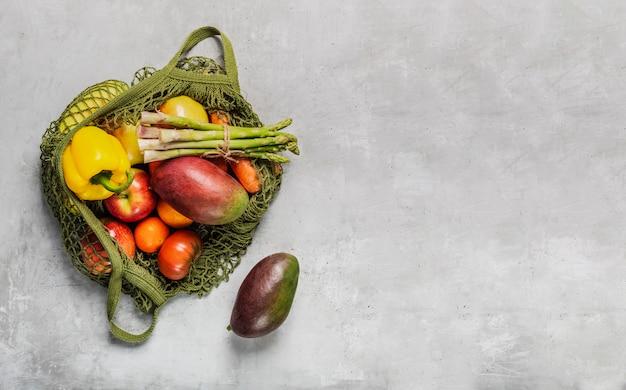 ライトグレーのテーブルに緑のひもバッグで新鮮な野菜や果物。プラスチックではなく、天然素材と天然物のみ。