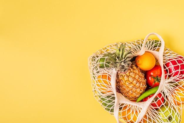 Свежие овощи и фрукты в сетке мешка, вид сверху.