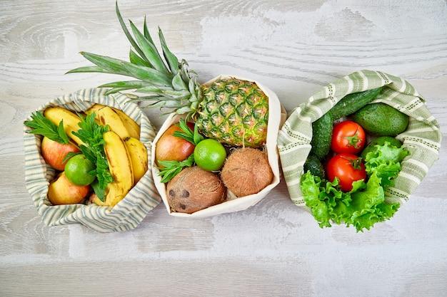 Свежие овощи и фрукты в эко хлопковых мешков на столе в кухне.