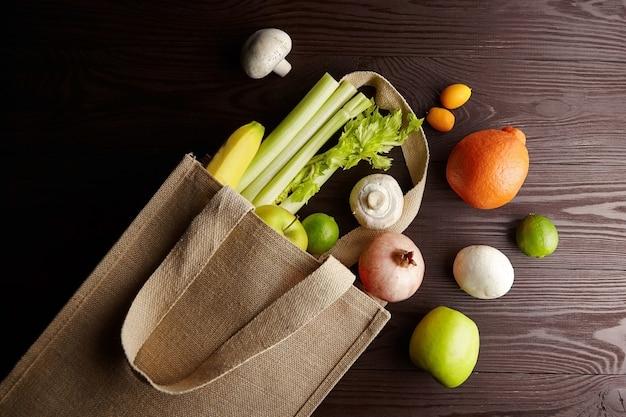Свежие овощи и фрукты в многоразовой хозяйственной сумке на деревянном столе