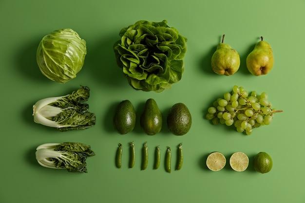 Свежие овощи и фрукты на ярко-зеленом фоне. спелые груши, виноград, лайм, капуста, салат из салата, горох и бок-чой для здорового питания. креативный макет. бакалейные и экологически чистые продукты.