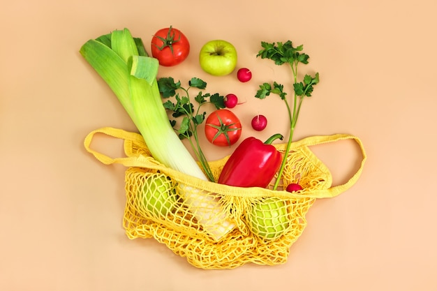 Свежие овощи и фрукты на эко-авоське на бежевой поверхности