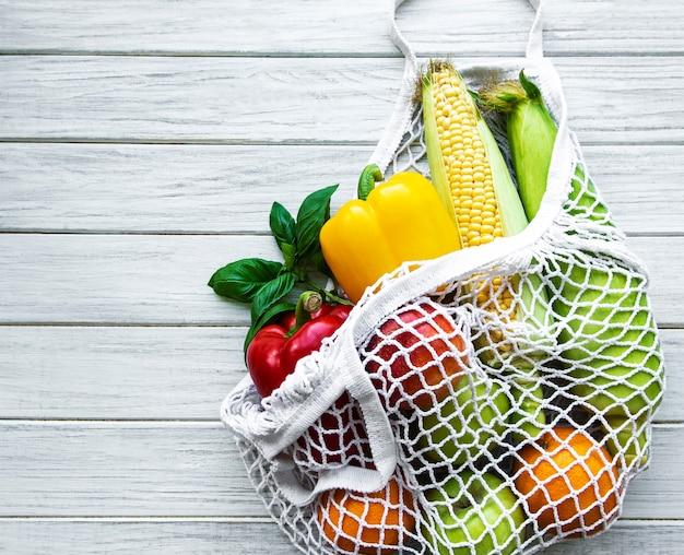 白い木製のエコストリングバッグに新鮮な野菜や果物。