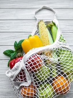 Свежие овощи и фрукты на эко-авоське на белом деревянном