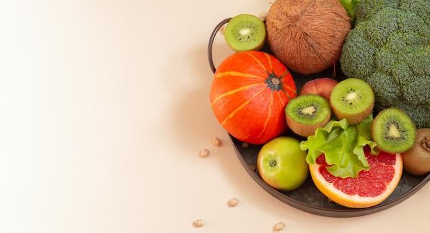 金属製のトレイに新鮮な野菜や果物。健康的な食事の概念