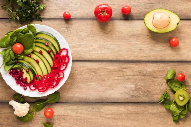 木製のテーブルの上の白い皿に新鮮な野菜や果物のサラダ