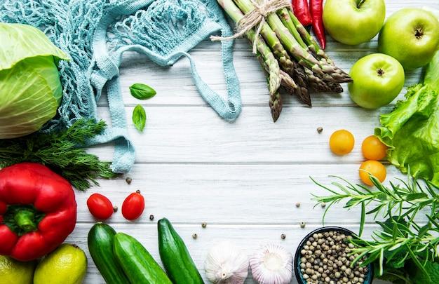 Свежие овощи и фрукты с авоськой на белой деревянной поверхности. здоровый образ жизни. вид сверху. никаких отходов.