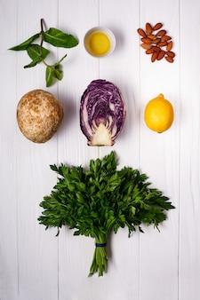 新鮮な野菜と白い木製の表面の上の緑