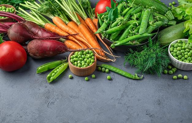 Свежие овощи и зелень на синем фоне. здоровые диетические продукты. вид сбоку, место для копирования.