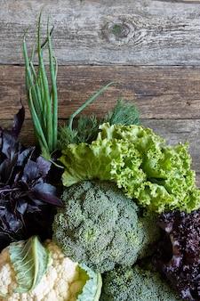 新鮮な野菜とハーブの古い大まかな木製の表面、健康的な食事の概念、選択と集中
