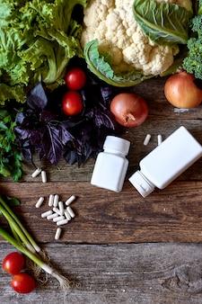 新鮮な野菜とハーブの古い大まかな木製の表面、散在する錠剤と錠剤、健康的な食事の概念、選択と集中のためのチューブ