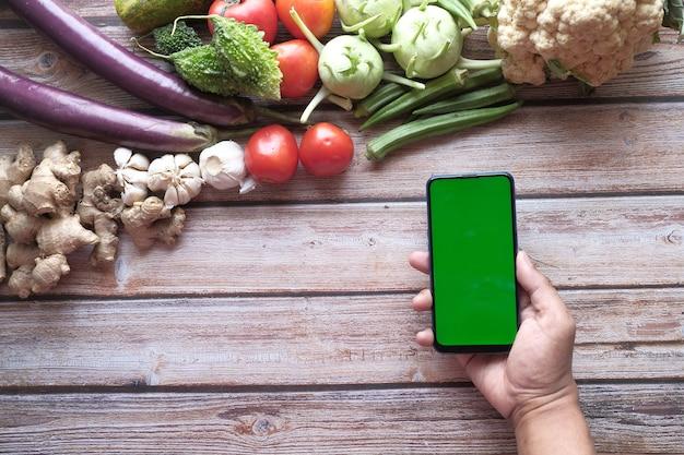 Свежие овощи и мобильный телефон с зеленым экраном на столе