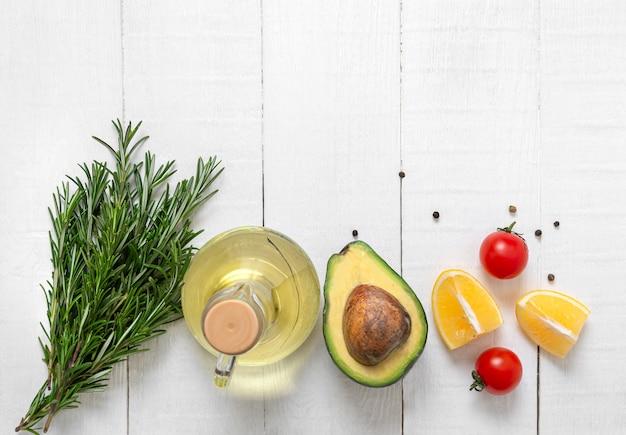 白い木製のテーブルで調理するための新鮮な野菜や食材。ベジタリアンと健康的な食事の概念。