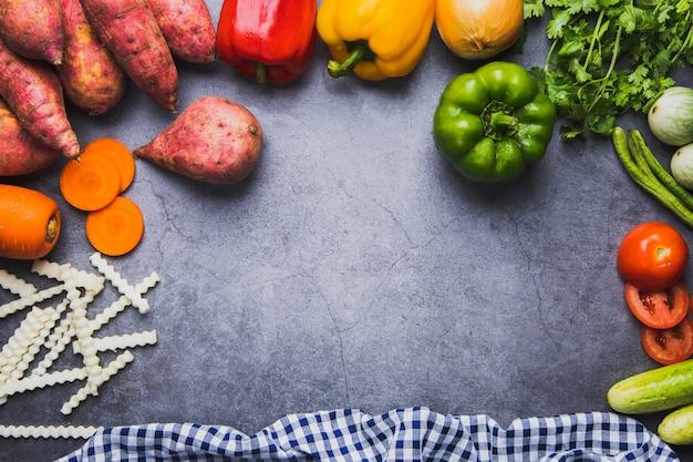 Свежие овощи и вид сверху смешивают натуральное питание на темном цементном полу, концепцию чистой еды и хорошую здоровую еду для меню