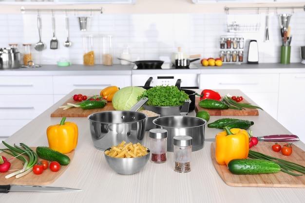 나무 테이블에서 요리 수업을 위한 신선한 야채와 기구