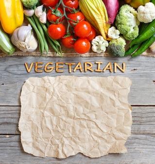 コピースペースを持つ古い木製テーブルトップビューで新鮮な野菜と木製の手紙