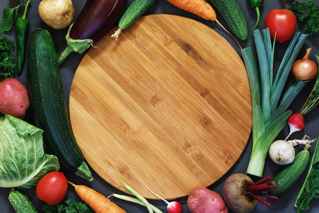 Fresh vegetables are laid out around a cutting board with space for text