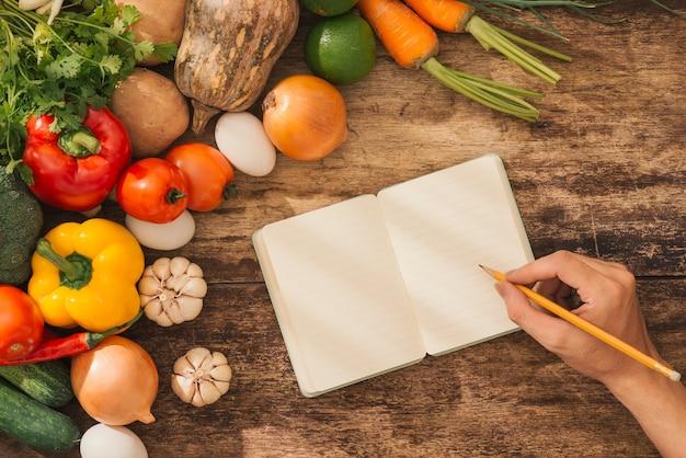 Свежие овощи вокруг открытого ноутбука на деревенском фоне