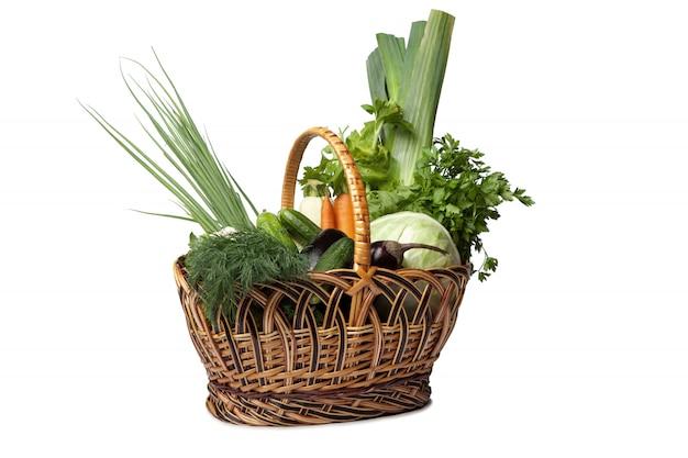 Fresh vegetables in a basket fruit on white