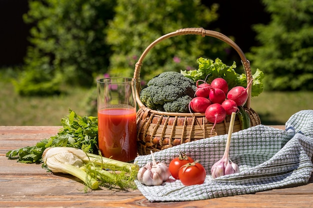 Fresh vegetables in a basket and tomato juice over green nature.