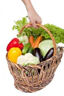 Fresh vegetables in a basket on white.