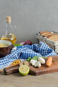 Verdure fresche, pane, olio e tagliatelle sulla tavola di legno