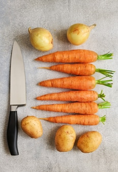 Fresh vegetables and a chefs knife are on the table, top view