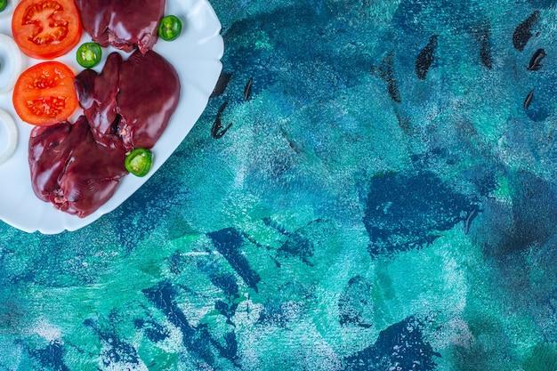 Verdure fresche e fegatini di pollo su un piatto