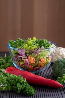 Нарезанные в стеклянной миске свежие овощи с помидорами и петрушкой на переднем плане с местом для текста сверху