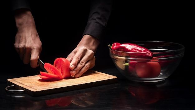 신선한 야채. 요리와 레스토랑에서 요리사로 일하는 동안 육즙 토마토를 자르고 젊은 남자의 손을 닫습니다.