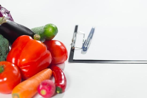 신선한 야채 구성과 흰색 배경에 격리된 다이어트 계획이 있는 노트북. 건강 식품 광고