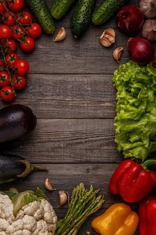 Fresh vegetables for cooking on dark wooden background.