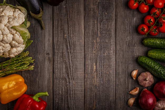Fresh vegetables for cooking on dark wooden table