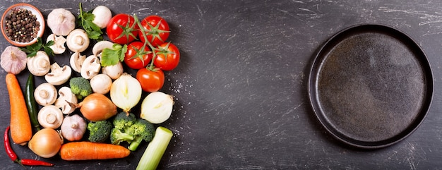 Fresh vegetables for cooking and empty pan on dark table, top view with copy space