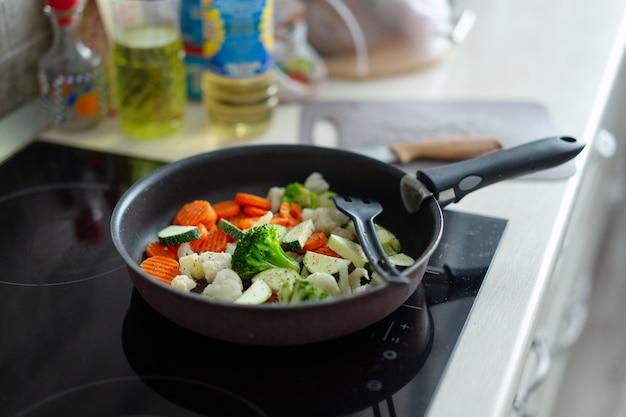 Приготовление свежих овощей на сковороде на домашней кухне. крупный план.