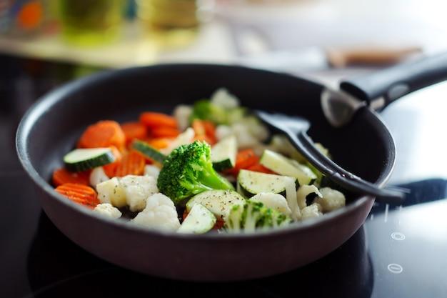 家庭の台所で鍋で調理する新鮮な野菜。閉じる。
