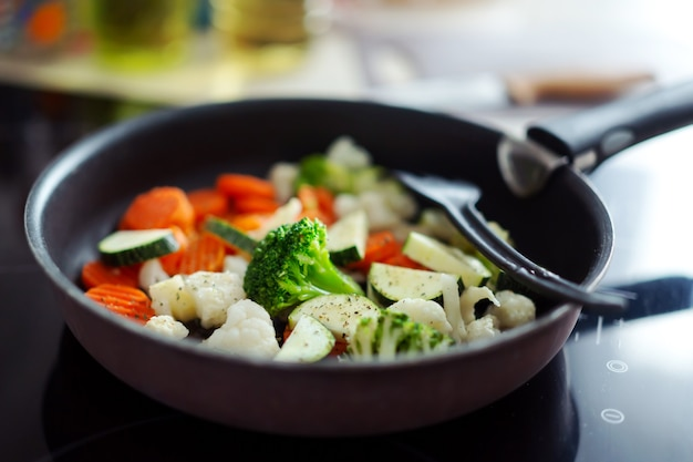 Fresh vegetables cooking on pan at home kitchen. closeup.