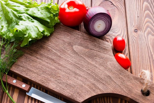 Fresh vegetables next to a cutting board on a wooden