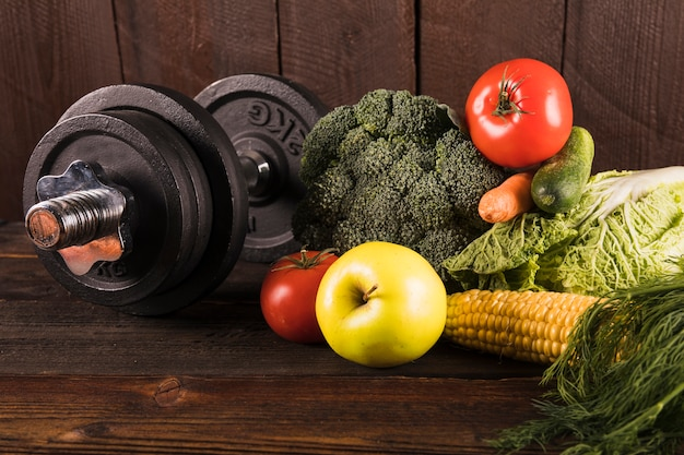 Fresh vegetables and dumbbells on wooden background