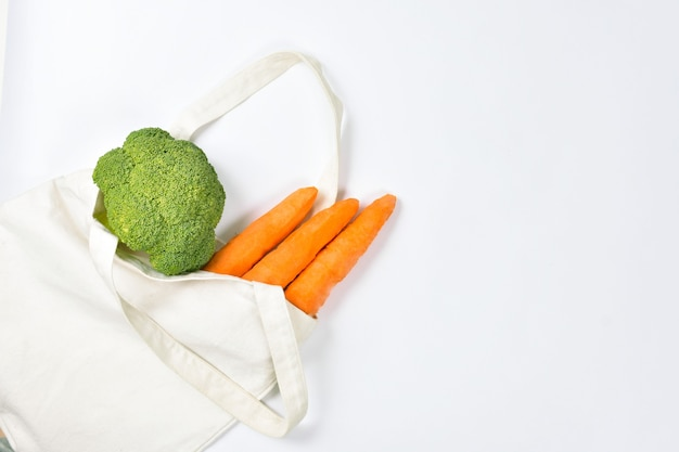 Fresh vegetables in an eco friendly beige tote bag on white wall,. zero waste concept. copy space, flatly.