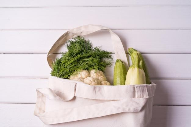 Fresh vegetables in eco reusable zero waste textile shopping bag over white table, horizontal orientation.