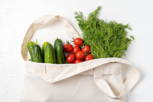 Fresh vegetables in eco reusable zero waste textile shopping bag over white
