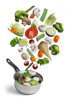 Fresh vegetables flying in a pot, isolated on white
