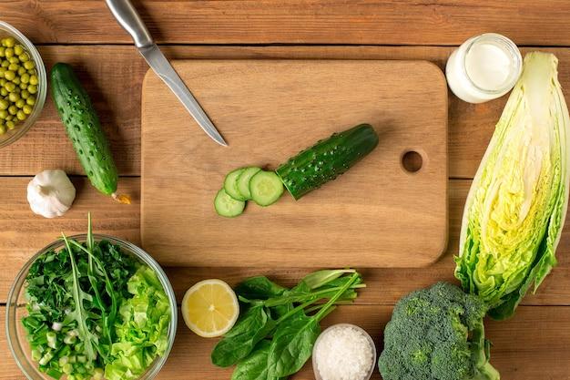 샐러드에 대 한 신선한 야채는 커팅 보드와 함께 나무 테이블에 놓여 있습니다. 평면도.