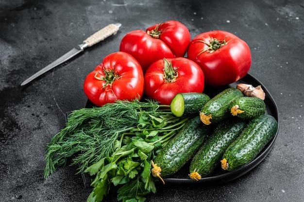 여름 그린 샐러드, 빨간 토마토, 오이, 파슬리, 허브를 위한 신선한 야채. 검은 배경. 평면도.
